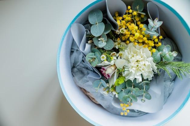 咲くミモザの花束、カーネーション。コピースペース。鮮やかな花束の平面図。特別イベントへのプレゼント