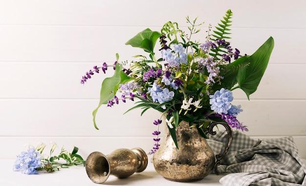 テーブルの上の投手の近くの花瓶に花の花束