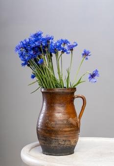 테이블에 꽃병에 파란색 수레 국화의 꽃다발