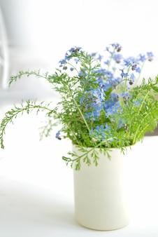 창턱에 꽃병에 푸른 물 망 초 야생화의 꽃다발