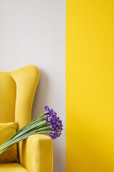 黄色の椅子の背景に青い菖蒲の花束。誕生日、3月8日女性の日、愛とお祝いのコンセプト。縦書きのテキスト用のコピースペース付き