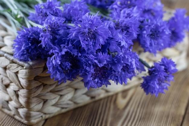 고리 버들 세공 바구니에 밝은 파란색 꽃의 꽃다발
