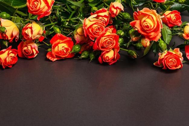 검은 돌 배경에 밝은 오렌지 장미 꽃다발.