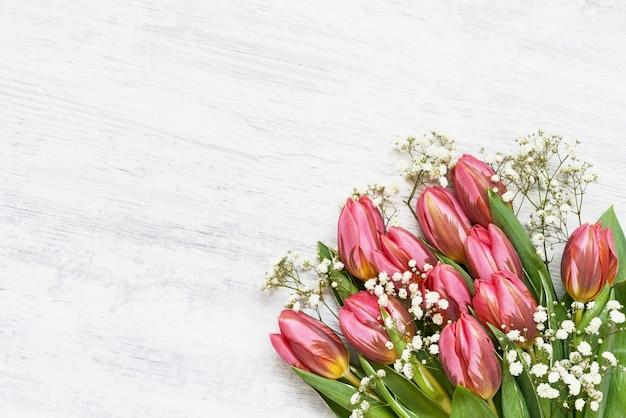 白い木製の背景に明るいピンクのチューリップとカスミソウの花の花束。上面図、コピー
