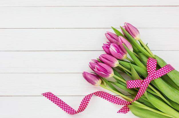 흰색 나무 바탕에 밝은 핑크 튤립 꽃다발. 평면도, 복사 공간