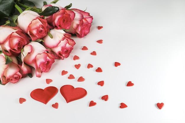 白い背景の上の明るいバラと赤いハートの花束。バレンタインデーのグリーティングカード。