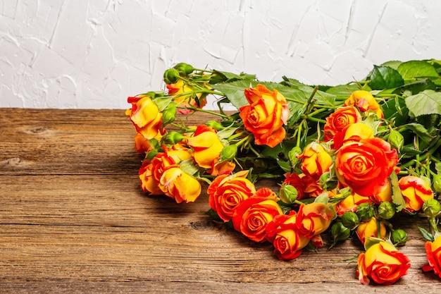 오래 된 나무 테이블에 밝은 노란색 장미 꽃다발