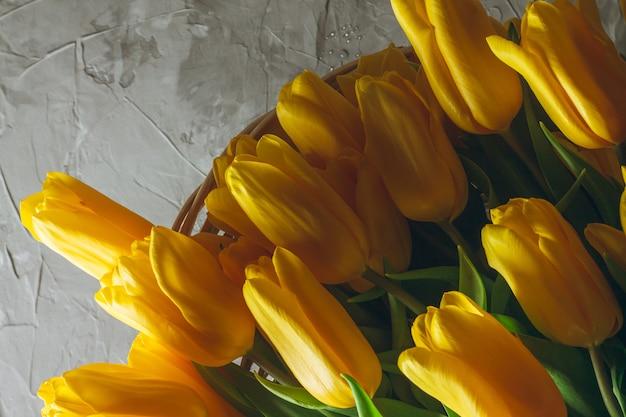 Букет ярко-желтых тюльпанов в плетеной корзине на серой бетонной стене. вид сверху. копировать пространство