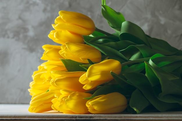 Букет из ярко-желтых тюльпанов, лежащих на белой деревянной поверхности на серой стене. копировать пространство