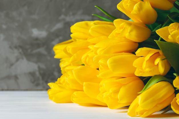 Букет из ярко-желтых тюльпанов, лежащих на белой деревянной поверхности