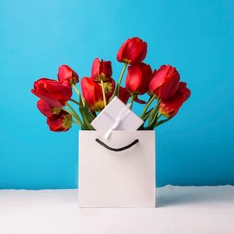 Букет из ярко красных тюльпанов в белой подарочной сумке на синем. концепция поздравления, сюрприза и подарка