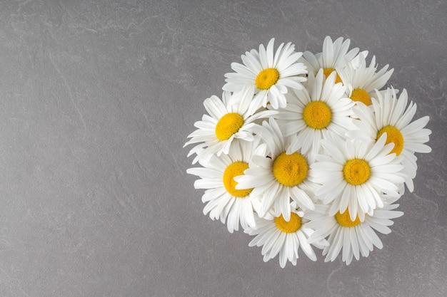 お祝いのお祝いのコピースペースのための灰色のテーブルトップビューデイジーの花のカモミールの花束