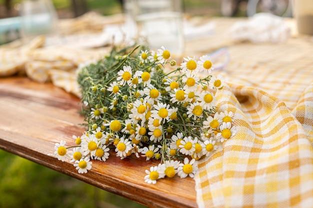 市松模様のテーブルクロスと屋外テーブルのカモミールの花の花束