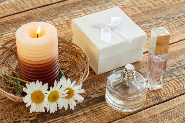 카모마일 꽃다발, 향수, 불타는 초, 나무 판자에 있는 흰색 선물 상자. 평면도. 휴일 개념입니다.