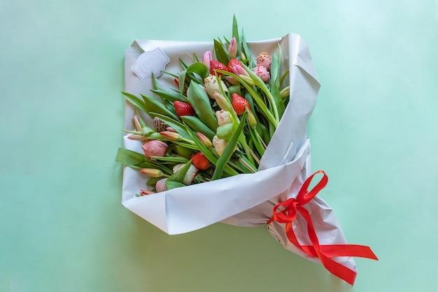 Букет из клубники и тюльпанов в шоколаде на зеленом фоне