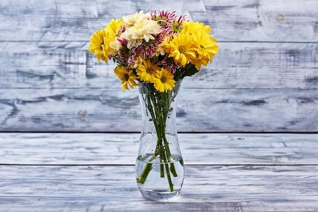 국화 꽃다발입니다. 유리 꽃병에 다채로운 꽃입니다. 꽃이 만발한 인테리어 디테일.