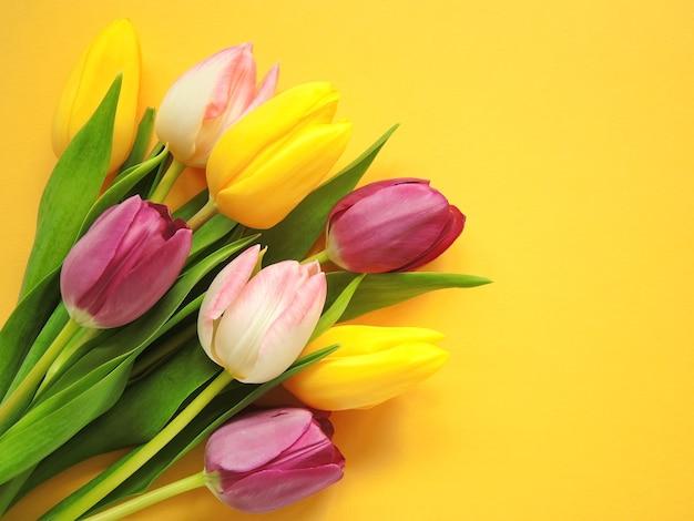 黄色の背景に色のチューリップの花束