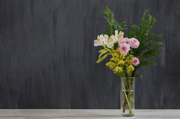 Букет ярких цветов в стакане с черным винтажным фоном