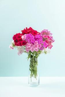 파란색 바탕에 꽃병에 화려한 꽃의 꽃다발. 공간 복사 최소한의 스타일. 엽서, 텍스트, 디자인 템플릿
