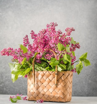 籐のバスケットに色とりどりのライラックの花の花束。春夏のコンセプト。花、インテリア、自然