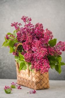 籐のバスケットに色とりどりのライラックの花の花束