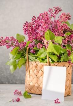 籐のバスケットにカードとカラフルなライラックの花の花束
