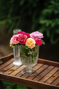Букет разноцветных роз в стеклянной вазе на ножке на деревянном подносе