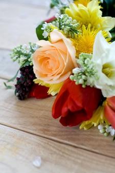 未塗装の木製テーブルの上に横たわるカラフルな春の花の花束