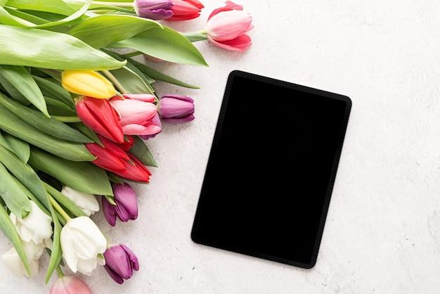 カラフルなチューリップの花とデジタルタブレットの上面図フラットレイの花束