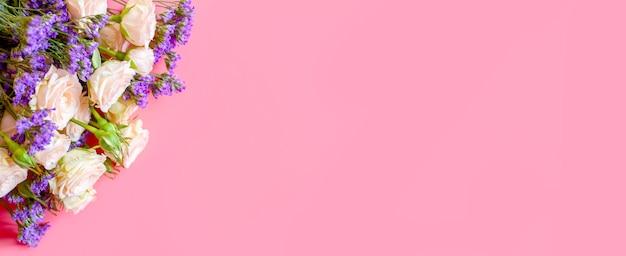 クリーム色のバラとピンクの背景に満開の明るい紫色の花の花束