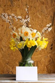 水仙と開花プラムの花束は、コピースペースのある木製のテーブルの上に空白のガラスの瓶を分岐します