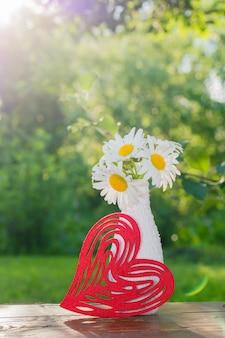 Букет из ромашек в белой вазе, украшенный вязанием, и красное фигурное сердце на столе