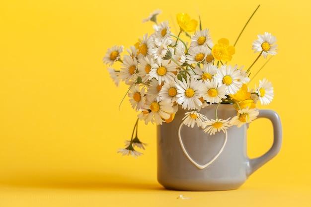 Букет цветов ромашки в серой чашке на желтом фоне