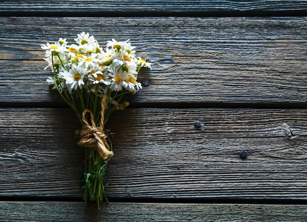 木製の背景にデイジーの花の花束