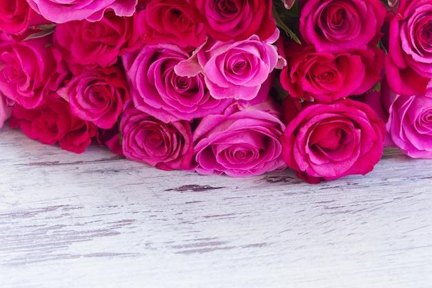 濃い色と薄いピンク色の新鮮なバラの花束は、白い木製の老化した背景に接しています