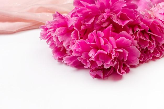 Букет из темно-розовых цветов пиона крупным планом и розовой ткани на белом фоне с копией пространства