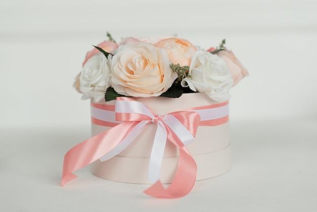弓が付いている丸いピンクの箱の装飾的な花の花束