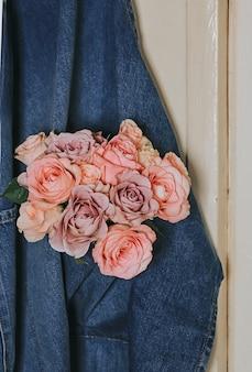 데님 주머니에 섬세한 장미 꽃다발.