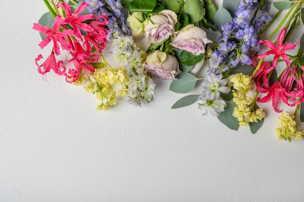明るい背景の上にさまざまな花の花束。上面図。コピースペース