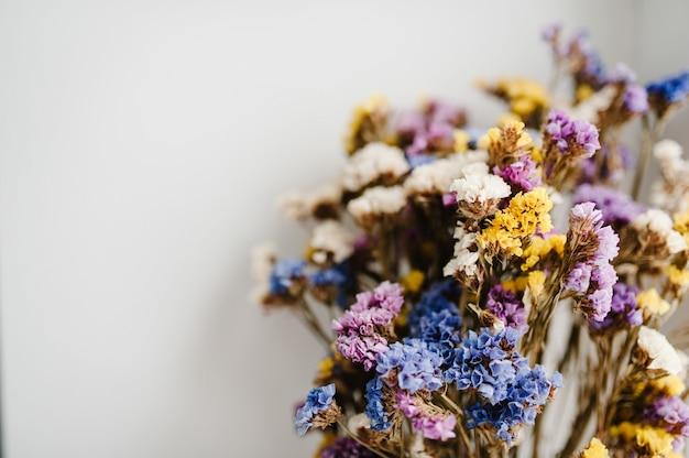 Букет из засушенных разноцветных цветов, лежащих на белой поверхности стола