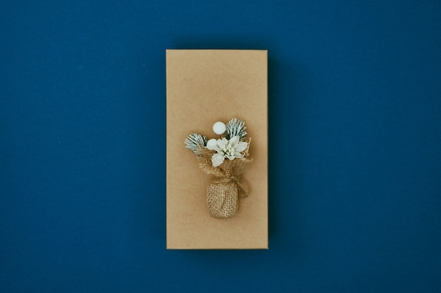 青い背景のギフトボックスにドライフラワーの花束新年の装飾コピースペースフラットレイモックアップ上面図