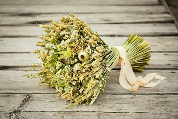 Букет из засушенных цветов. натюрморт с колосьями пшеницы и желтыми и белыми полевыми цветами.