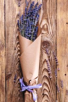Букет сушеной лаванды в крафт-бумаге на деревянном фоне вид сверху вертикальное фото