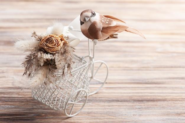 복사 공간 저 작은 갈색 새 장식 자전거에 마른 꽃의 꽃다발. 자연스러운 색조의 결혼식이나 휴가를위한 인사말 카드