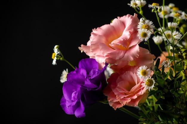 黒の背景の上のテーブルにツゲの木と小さな葉の枝を持つトルコギキョウの花束