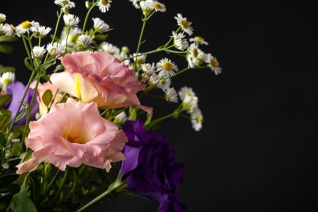 黒の背景の上のテーブルにツゲの木と小さな葉の枝とトルコギキョウの花束