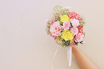 Bouquet of flower in hand and white wall with retro filter effect