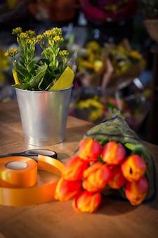 木製のテーブルにはさみとポリリボンと花の花束