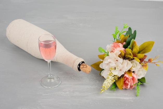 花の花束と灰色の表面にロゼワインのグラス