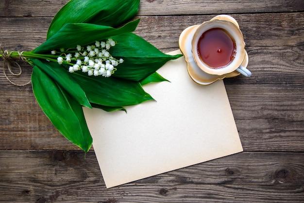 나무 배경에 종이와 꽃과 차 컵의 꽃다발